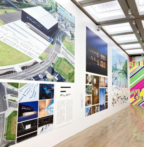 20年4月に開業した青森県八戸市の多目的アリーナ「FLAT HACHINOHE(フラット八戸)」(手前)。SAMURAIがロゴデザインだけでなく、空間デザインをプロジェクトの初期段階から入り込んで手掛けた。建物の設計・施工は戸田建設が担当。展示中央が「千里リハビリテーション病院」、奥が「ふじようちえん」の展示(写真:SAMURAI)