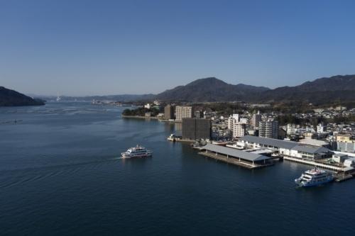 海辺に、灰色の勾配屋根を架けた2つの施設が建つ。そのうち、右奥が「宮島口旅客ターミナル」。海沿いの施設は、広島湾に突き出した桟橋と乗り場だ。屋根の形状をそろえることで、ターミナル施設と桟橋、周辺にある建物などの調和を図った(写真:阿野 太一)