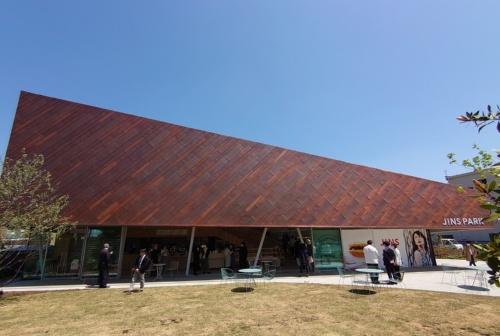 芝生の屋外広場「ひろば」から見た建物。見る角度によって異なる形に思える(写真:日経クロステック)
