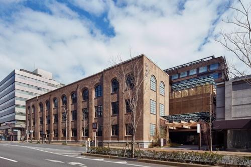 烏丸通から見た「新風館」。地上3階建ての京都市登録文化財「旧京都中央電話局」と、背後の新築棟から成る。右手は烏丸通のエントランス。東側の東洞院通とはパサージュで結ばれ、相互に通り抜けできる。京都市営地下鉄の烏丸御池駅とはエレベーターで直結する(写真:Forward Stroke)