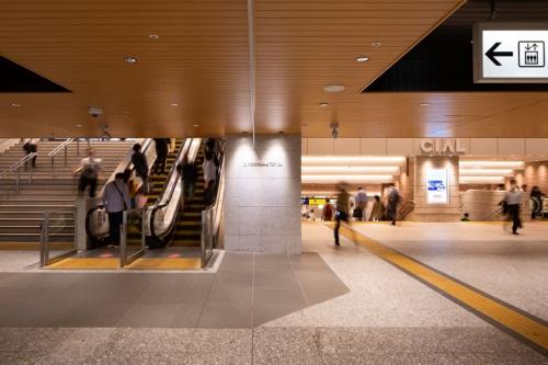 横浜駅の中央通路から見た地下動線。写真左のエスカレーターで、JR横浜タワー1階の吹き抜けに上がる。写真右は駅西口の地下街へと続く通路(写真:浅田 美浩)