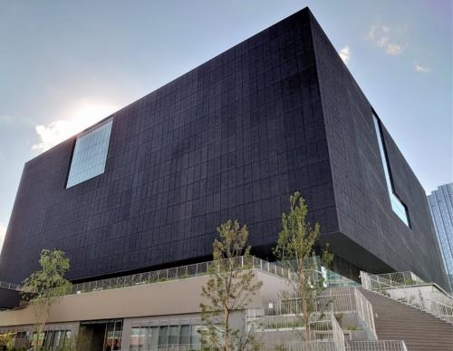 真っ黒な四角い建物。黒い箱が浮いているように見える。黒い外壁の表面は凹凸があり、ざらついている(写真:日経クロステック)