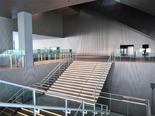 上ってきた階段を見下ろす。奥の通路が2階のパッサージュ。館内のパッサージュは2階を中心に上下につながり、巨大な空間を生み出している。2階のパッサージュを右に進むと、外の芝生広場に出られる(写真:日経クロステック)