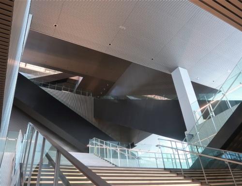 階段の途中から館内を見上げると、複雑に入り組んだ壁や柱、そして真っ黒なエスカレーターが目に飛び込んでくる(写真:日経クロステック)