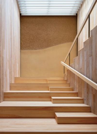 突き当たりの既存壁面を取り除き、2階への階段室を増築した。ここは左官職人による土壁の仕上げにし、階段を上り下りするのが楽しくなる工夫をした(写真:浅沼組)