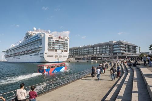 横浜ハンマーヘッドの外観(写真右奥)。2019年11月4日には開業後初めて客船が着岸した(写真左)。英国船籍の客船で、名称は「ダイヤモンド・プリンセス」。全長290m、乗客定員は2706人だ(写真:日経アーキテクチュア)