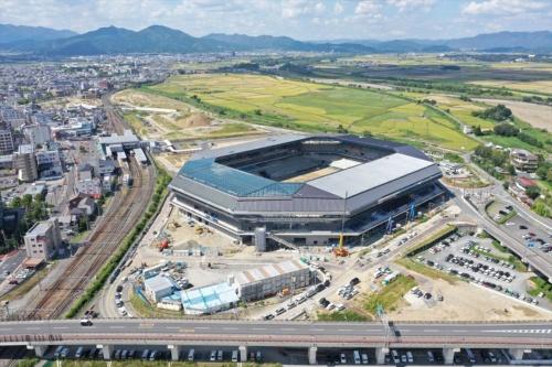 東畑建築事務所が設計を手掛け、京都府亀岡市に2019年12月竣工予定の「京都スタジアム(仮称)」は、「みんなの笑顔がきらめくコンパクトスタジアム」がコンセプト。最高の観戦環境の創出、周辺環境への影響の最少化、ライフサイクルコストの低減を実現する計画だ。敷地形状に合わせて四隅を大きく切り取った八角形のスタンド形状によって、効率的に観客席数を確保。全ての観客席を覆う屋根は、スタンド先端からさらに2m突き出し、雨天時も快適に観戦できる。高さを抑えた屋根の多面体の構成や台形のシルエットは、亀岡盆地の山並み風景との調和を図っている(写真:東畑建築事務所)