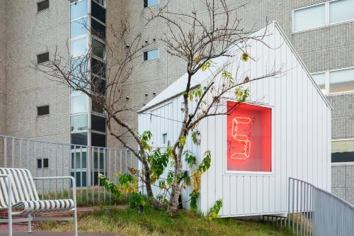 新棟てっぺんの小屋は、アートの展示室になっている。緑の丘の階段を上って小屋まで行く。ここには宿泊者だけが立ち入れる(写真:Shinya Kigure)