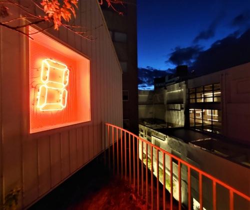 夜には、デジタルカウンターを用いた宮島達男氏のアート作品が輝く。既存棟の中の光るパイプも新棟側から見える(写真:日経クロステック)