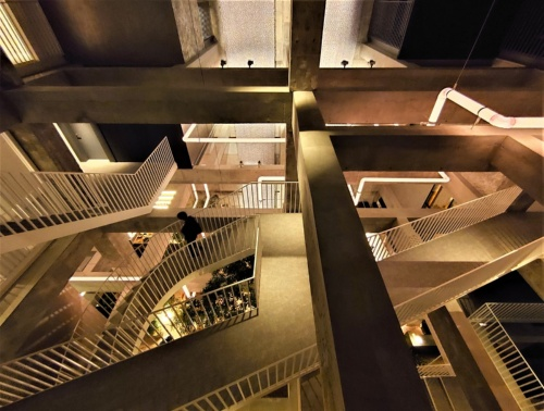 夜の吹き抜け空間。コンクリートの躯体と光るパイプのアートが調和している(写真:日経クロステック)