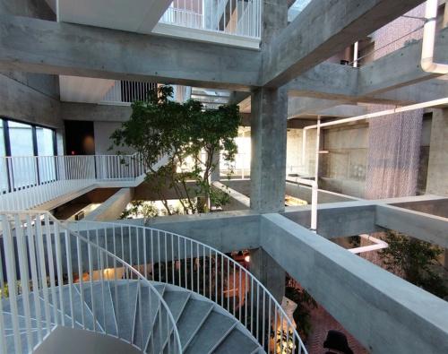 コンクリートの躯体と様々な方向に延びる階段や通路、多彩な植物の緑、パイプを模したアート、巨大なテキスタイルなどが吹き抜け空間に入り交じる。パイプはアーティストのレアンドロ・エルリッヒ氏が白井屋ホテルのために制作したサイトスペシフィックアート「Lighting Pipes(ライティングパイプ)」。かつて躯体の回りに配管が張り巡らされていたことに着想を得た作品(写真:日経クロステック)