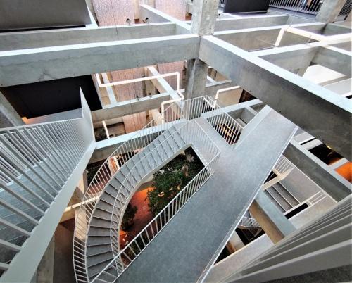 まるで「だまし絵」のような、白井屋ホテルの吹き抜け空間。床を解体して既存躯体(くたい)の柱や梁(はり)を現(あらわ)しにし、らせん階段や空間を斜めに横切るブリッジを設けた(写真:日経クロステック)