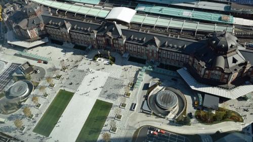 """南西側から俯瞰(ふかん)した東京駅丸の内駅前広場。同広場は駅舎の復元から約5年後の2017年12月7日に完成した。真っ白な""""帯""""は広場の西端(下方)まで延びる。帯の駅舎側端部の両脇には夏場、水が張られる(写真:日経コンストラクション)"""