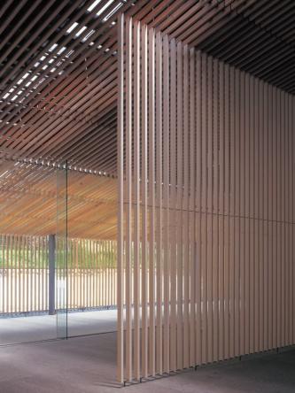 エントランスホールから風除室の方向を見る。スギのルーバーの重なりが特徴。そろそろ分かりましたか?(写真:三島 叡)