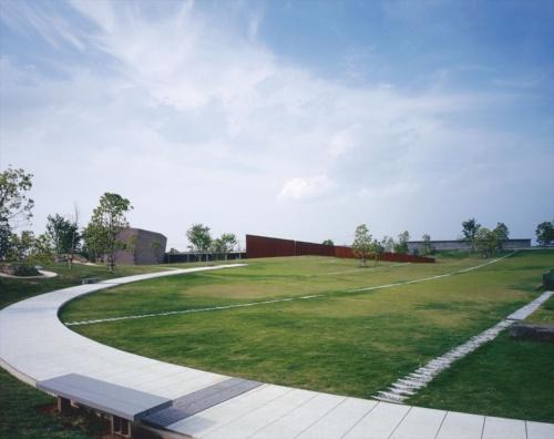 南側から見た全景。左から相原山首遺跡(古墳群)、葬斎場のホール、葬斎場の待合室や炉室。手前が楕円形の「アースディッシュ」。すり鉢状にわずかに傾斜している。開館当初(1997年)に撮影(写真:吉田 誠)