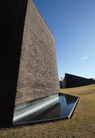 八角形平面のホールの外観。外壁はれんが積み。足元の水盤は、ホール内に太陽光を反射させる。以下の写真とも2018年12月に撮影(写真:日経アーキテクチュア)