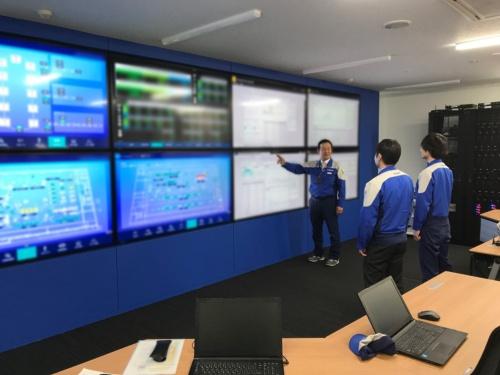 安川ソリューションファクトリの「統合司令室」。写真は、モーションコントロール事業部モーションコントロール工場の白石聡工場長(左)がモニターの前で部下と議論している様子