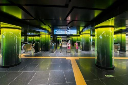黒を基調とした改札口の周辺には、各路線を象徴するラインカラーで鮮やかにライトアップしたガラス張りの柱が並ぶ。写真は銀座線の改札口(写真:大上 祐史)