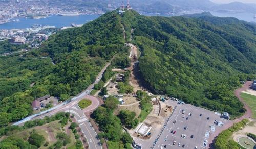 稲佐山を北側から望む。写真左奥に長崎の街や港が見える。長崎市は手前の駐車場から山頂まで、新たな輸送手段を整備した。写真は施工中の様子(写真:長崎市)