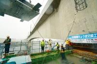 新たに設置する免震支承の大きさは1辺が2mで、重さは約30t。滝のように降り注ぐ大雨の中で工事は進んだ(写真:日経コンストラクション)