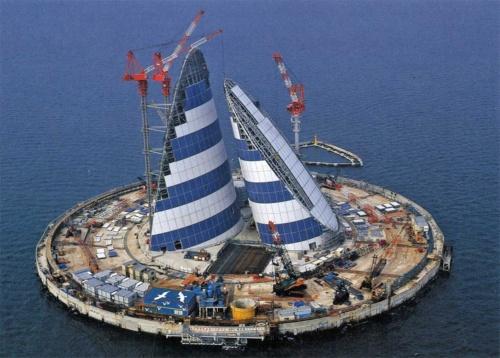 斜め上空から見た川崎人工島。島の直径は195mで、海面下約50mの海底地盤にトンネルが通っている。換気塔は「風の塔」とも呼ばれ、日本画家の平山郁夫氏などがデザイン決定に関わった(写真:三島 叡)