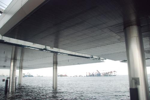 施工中の桟橋部を見上げたところ。脚部はステンレス鋼のライニング、桁下はチタン製のカバープレートで覆われている。桁下の空間は除湿機を使って湿度を50%以下に抑える(写真:日経コンストラクション)