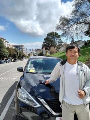筆者とリフトの車両。サンフランシスコの市庁舎を望むアラモ・スクウェア公園のフルトン通りで撮影