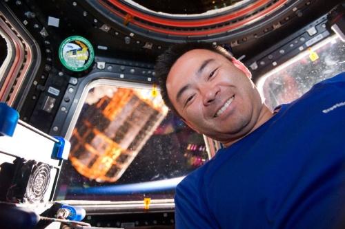 ISSのロボットアーム(SSRMS)に把持された宇宙ステーション補給機「こうのとり」3号機(HTV3)と星出彰彦宇宙飛行士。星出氏の左側の金色の物体がこうのとり