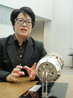 宇宙航空研究開発機構(JAXA)で宇宙ステーション補給機「こうのとり」(HTV)のフライトディレクタを務める前田真紀氏。手前にあるのがこうのとりの模型