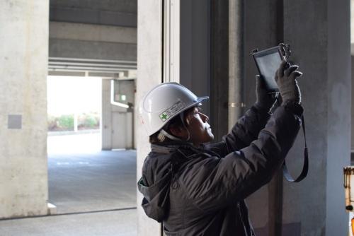 施工現場でタブレットを使う向洋電機土木の社員