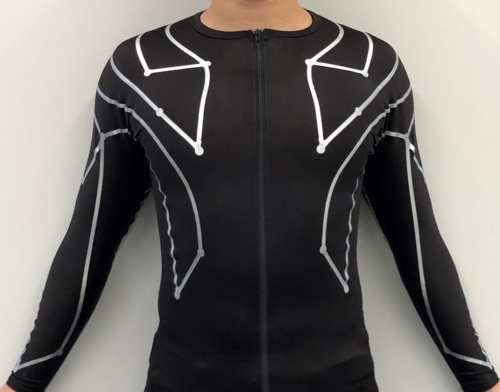 アシックスとXenomaが開発した、着て投げるだけで投球動作を解析できる「投球動作解析 e-skinシャツ」。見えている銀色の部分は配線ではなく絶縁材で、その下の凹凸部分が配線。そして配線のない部分が歪みセンサーである。例えば、手首に近い部分や肋骨の下あたりに斜めに張り付けてあるのがそれだ