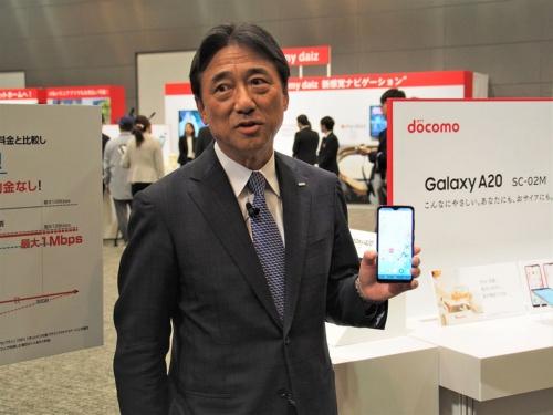 「Galaxy A20」をアピールするNTTドコモ 代表取締役社長の吉澤和弘氏。2019年の秋冬商戦向けモデルでは、低価格のスタンダードモデルを前面に打ち出した。写真は2019年10月11日のNTTドコモ新サービス・新商品発表会より(筆者撮影)