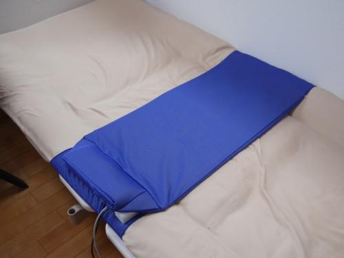 ベッドに置いた青いシート状のデバイスが排せつセンサーの「ヘルプパッド」