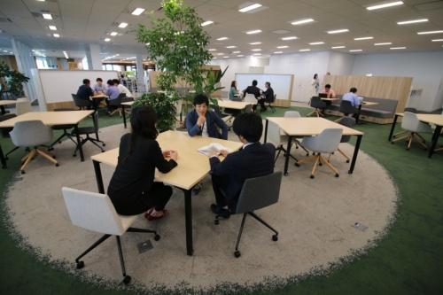 オフィスフロアの中心に設けた打ち合わせエリア。緑色のカーペットが目を引く。ロングシートやホワイトボードを組み込んだシェルフで仕切っている