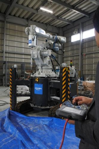 會澤高圧コンクリートが導入した3Dプリンター。ロボットアームはスイスのABB製、コントローラーはオランダのサイビー・コンストラクション製だ。造形テストを繰り返して、3Dプリンターの可能性や課題を探っている。履帯付きで自走できる。横2.5m×奥行き1.5m×高さ3mまでの造形が可能だ(写真:奥野 慶四郎)