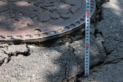路面が下がったためマンホールが浮き上がったように見える。2019年6月20日に撮影(写真:日経 xTECH)