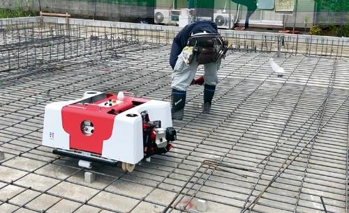 写真1■ ロボットは本体が左右に開き、100~300mm間の9種類の配筋ピッチに対応する。写真は最大となる300mmピッチを走行する様子(写真:EMO)