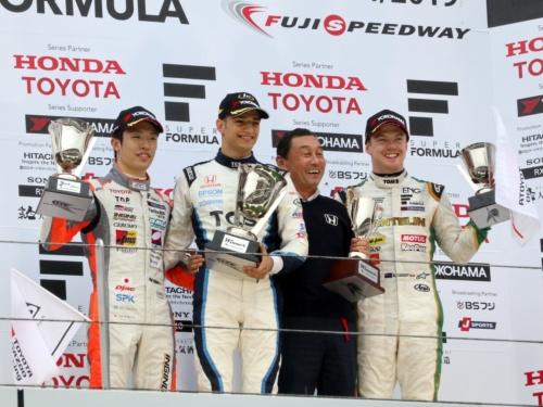 富士スピードウェイの表彰台で優勝トロフィーを掲げるTCSナカジマレーシングのアレックス・パロウ選手(左から2人目)と中嶋悟監督(同3人目)
