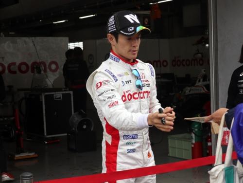 レース前にファンサービスをする山本尚貴選手。レース時はレーシングスーツの内側にhitoeを着用する