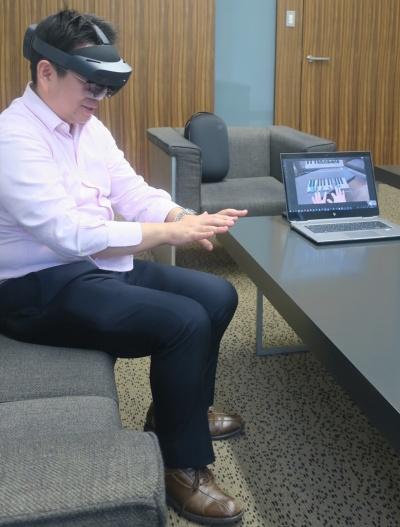 仮想の鍵盤でピアノを弾いてみた私。パソコンに映っているのは、私がHoloLens 2で見ている風景。鍵盤を確認できる(写真:日経アーキテクチュア)