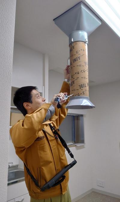 管理人室の天井にある換気扇の風速を測定しているところ。アリアテクニカの測定器「ワイヤレス風速・温度計」はBluetoothに対応しており、測定値は肩にかけたiPadに無線で自動入力される(写真:日経アーキテクチュア)