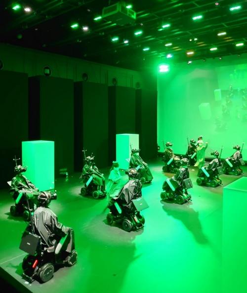 電動車椅子の列の間をダンサーが踊りながら走り抜ける。このシーンは、ヘッドマウントディスプレー(HMD)をかぶった体験者にどう見えているのか。この記事では極力、ネタばらしはしない。なお、写真や画像は全て本番前のもの(写真:日経クロステック)