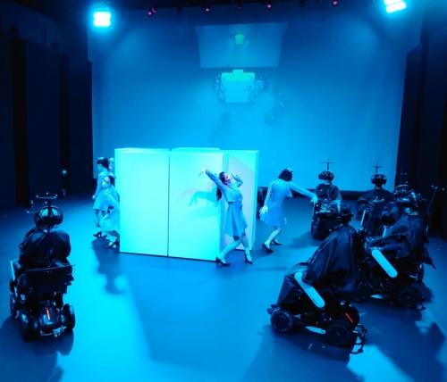 白いボックスの周りでダンサーが踊るシーン。写真のような客席からの眺めと、HMDで見ている世界は全く別物(写真:日経クロステック)