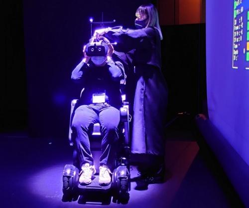 私(川又D)が電動車椅子に座り、HMDを装着しているところ(写真:日経クロステック)