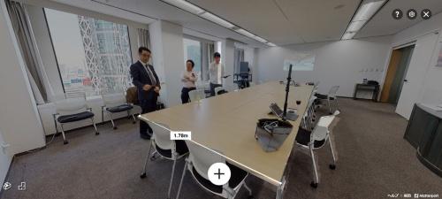 大成建設の会議室を私がマーターポートで撮影して回り、その場で360度画像に合成したもの。左が大成建設建築総本部生産技術推進部の田中吉史次長、中央が私、右がマーターポートを使った撮影サービス「3D+ONE」を手掛けるsognoのカメラマン。窓の外に見える建物は、外観が特徴的な東京モード学園のコクーンタワー(写真:大成建設)