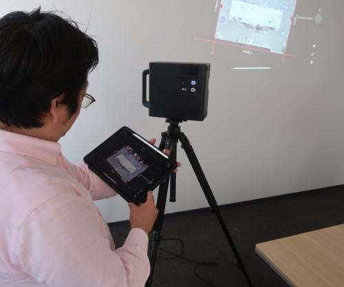 3D赤外線スキャンカメラをiPadで操作する私。撮影結果や合成画像は、その場でiPadに表示される(写真:日経アーキテクチュア)