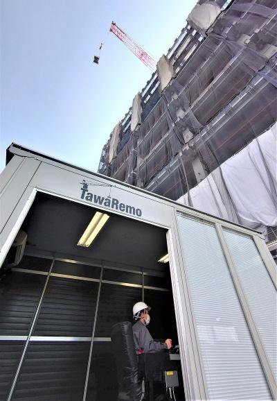 遠隔操作室の上空50mほどの高さまで、タワークレーンが仮設材を揚重しているところ(写真:日経クロステック)