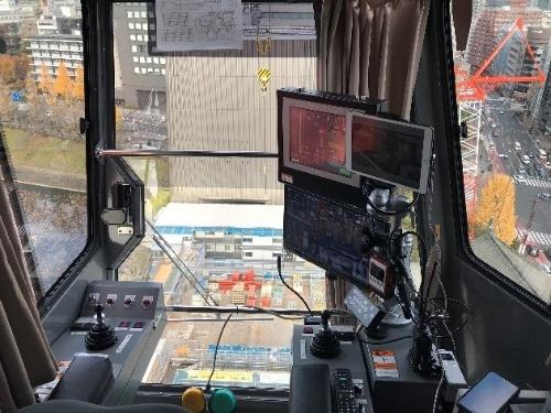 タワークレーンの運転席から見た実際の眺め。車が小さく見える(写真:鹿島、竹中工務店)