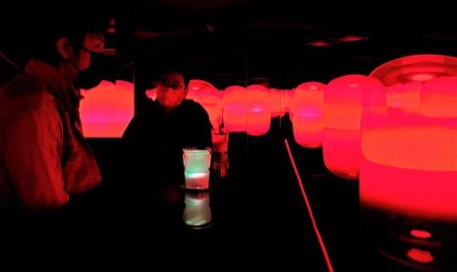 2週間ぶりに外出した猪子氏と、新作「TeamLab:Tea Time in the Soy Sauce Storehouse」の前で話をする私(右)。地下は真っ暗で、赤く光る無数のランプが水盤に浮かぶ光景とお茶のグラスだけが見える(写真:日経クロステック)