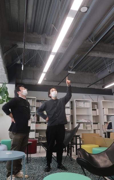 日建設計デジタルソリューションラボの大浦理路氏(右)が、自社の照明について私に説明してくれているところ。2人が照明の真下にいるので、照度が上がっている(写真:日経クロステック)